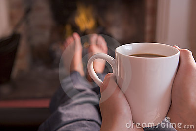 Feet warming at fireplace with coffee