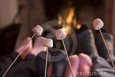Feet warming at a fireplace with marshmallows