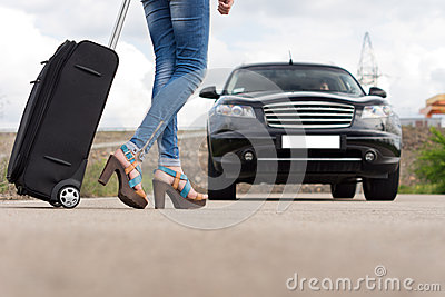 Feet of a woman carrying a black trolley case