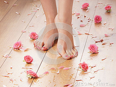 Feet of a young female on a wooden floor