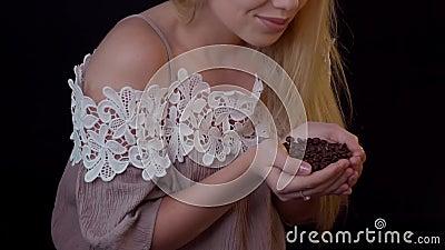 Feijões de café de cheiro - uma jovem mulher coloca-os em suas mãos vídeos de arquivo