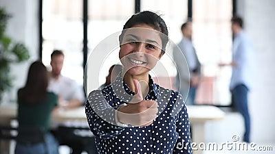 Felice e orgogliosa imprenditrice indiana professionista che mostra i pollici in ufficio video d archivio