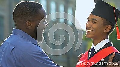Felice padre che guarda il figlio adolescente in abito magisteriale prima della cerimonia archivi video
