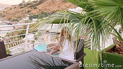 Felice ragazza seduta sotto le foglie di palma al balcone esterno con vista sul mare Ragazza sorridente sul balcone estivo in loc archivi video
