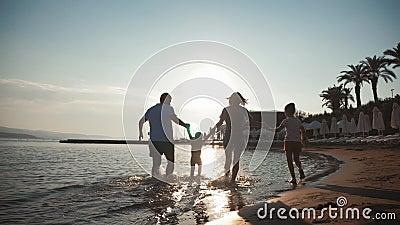 Felices familias jóvenes se divierten caminando por la playa al atardecer Viaje en silueta familiar almacen de video