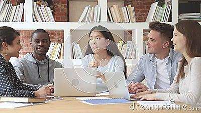 Felici studenti diversi che ascoltano il compagno di gruppo coreano asiatico video d archivio