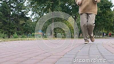 Feliz anciana trotando en el parque, actividad saludable al aire libre, bienestar de la vejez metrajes