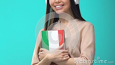 Feliz auscultador feminino estudante segurando livro italiano, seminário online, conhecimento video estoque