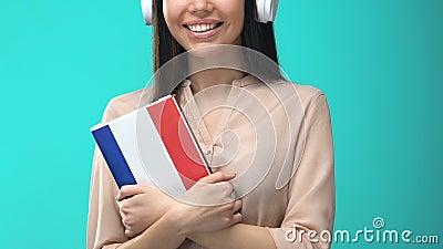 Feliz auscultadora estudante com o livro francês, seminário online, conhecimento vídeos de arquivo