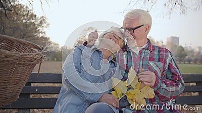 Feliz família madura caucasiana sentada no banco à luz do sol e falando Esposo europeu sênior a beijar o seu encantador filme