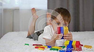 Feliz garoto alegre brincando com blocos coloridos enquanto deitado na cama Uma criança constrói a partir de mecano vídeos de arquivo
