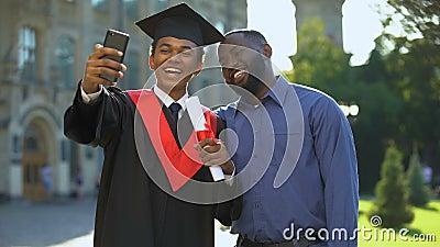 Feliz graduación universitaria, manto y padre tomando selfie smartphone almacen de video
