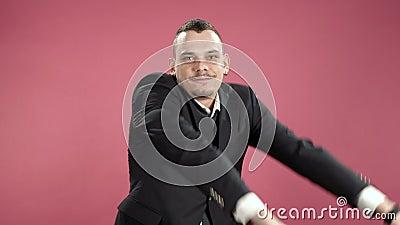 Feliz jovem a dançar de terno contra fundo rosa filme