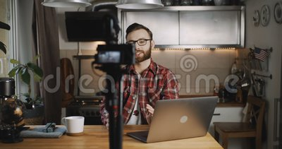 Feliz jovem e bem sucedido blogueiro profissional caucasiano sorri fazendo vídeo para o vlog usando câmera em casa em câmera lent vídeos de arquivo