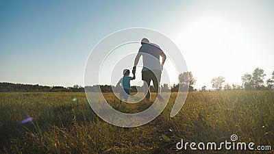 Feliz macho e garoto correndo no campo iluminado pelo sol Pai e seu filho andando em trilho entre o campo Conceito de família fel filme