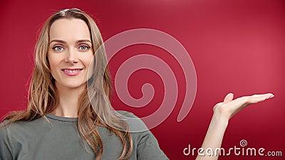 Feliz modelo casual europeo femenino que muestra un área de publicidad en brazos aislada en el estudio de fondo cerca almacen de metraje de vídeo