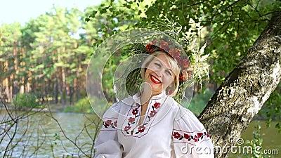 Feliz modelo rubio posando en círculo floral cerca del río metrajes
