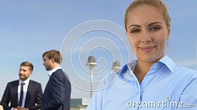 Feliz mujer de negocios sonriendo en cámara, colegas charlando sobre el fondo, la carrera almacen de video