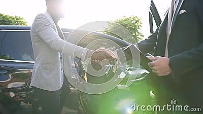 Feliz mujer guardando una llave sentada en el interior del auto y hombres dándose la mano entrando en un acuerdo de adquisición almacen de video