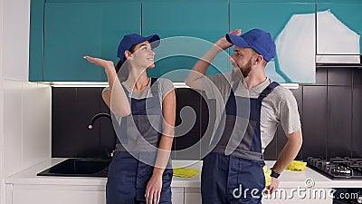 Feliz satisfez seu trabalho, homem e mulher do serviço de limpeza, dando cinco dólares na cozinha azul-negra video estoque
