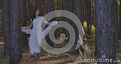 Feliz sorridente garota caucasiana girando entre as árvores da floresta de verão e sorrindo Misterioso independente filme