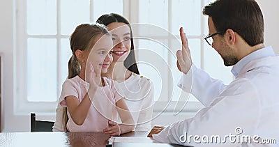 Feliz tierna niña linda le da cinco a un doctor varón. almacen de metraje de vídeo