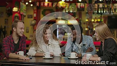 Felizes jovens multirraciais amigos falando rindo da reunião em grupo compartilhando mesa de café, diversos estudantes bebendo vídeos de arquivo