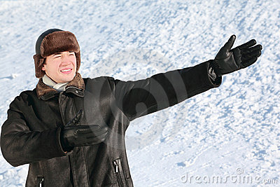 Fellow stands on snow, shows hands direction