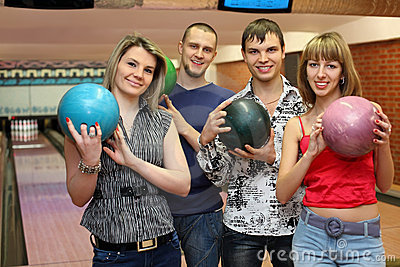 Fellows and girls stand hold balls for bowling