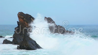 Felsen im Ozean und in einer großen Welle stock footage