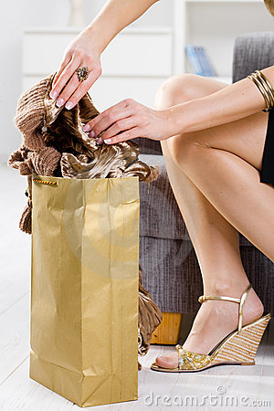 Femal hands packing out shopping bag