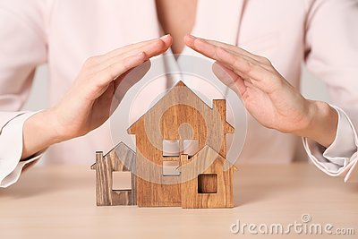 Female agent covering wooden houses at table. Home insurance Stock Photo