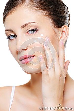 Female applying cosmetic cream on skin around eyes