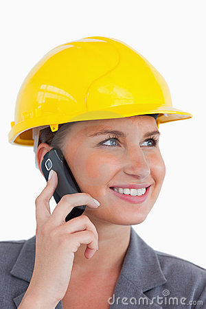 Female architect with cellphone and helmet on