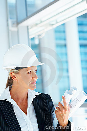 A female architect holding blueprints looking away
