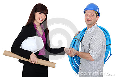 Female architect shaking electrician s hand