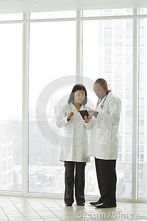 Female Asian doctor with African American doctor with tablet