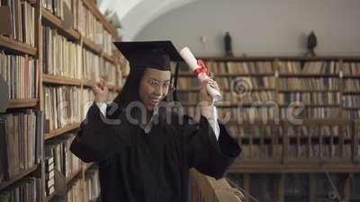 Female asian student lawyer in roung glasses and black gown holding. Scroll in her hand and enjoying her graduation in the library. Indoors. Portrait stock video footage