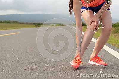 Female athlete ankle injury when running on road Stock Photo
