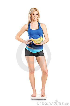 Female athlete on a weight scale holding bananas
