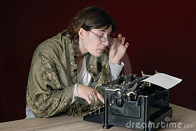 Female author typing on an old typewriter