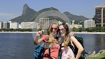 Female backpackers tourists with smartphone in Rio de Janeiro with Christ the Redeemer in background.