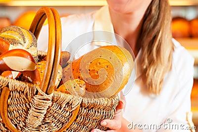 Female baker in bakery selling bread by basket