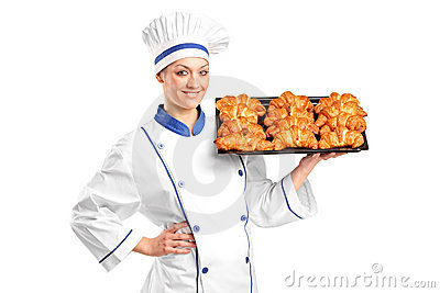 A female baker holding croissants