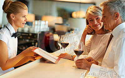 Female barmaid taking order from senior couple
