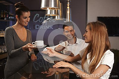 Female bartender serving young couple in bar