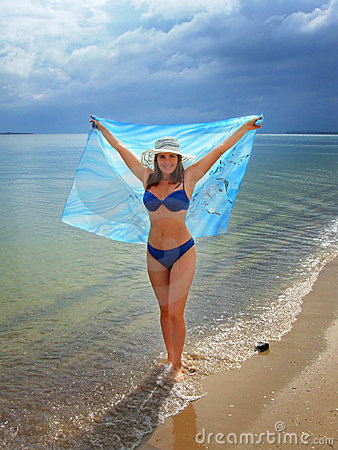 Female at the beach holding sarong
