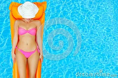 Female beauty relaxing in swimming pool