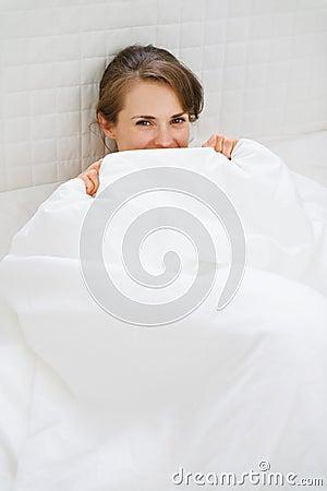 Female in bed hiding behind blanket