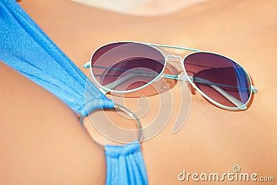 Female belly, bikini and shades